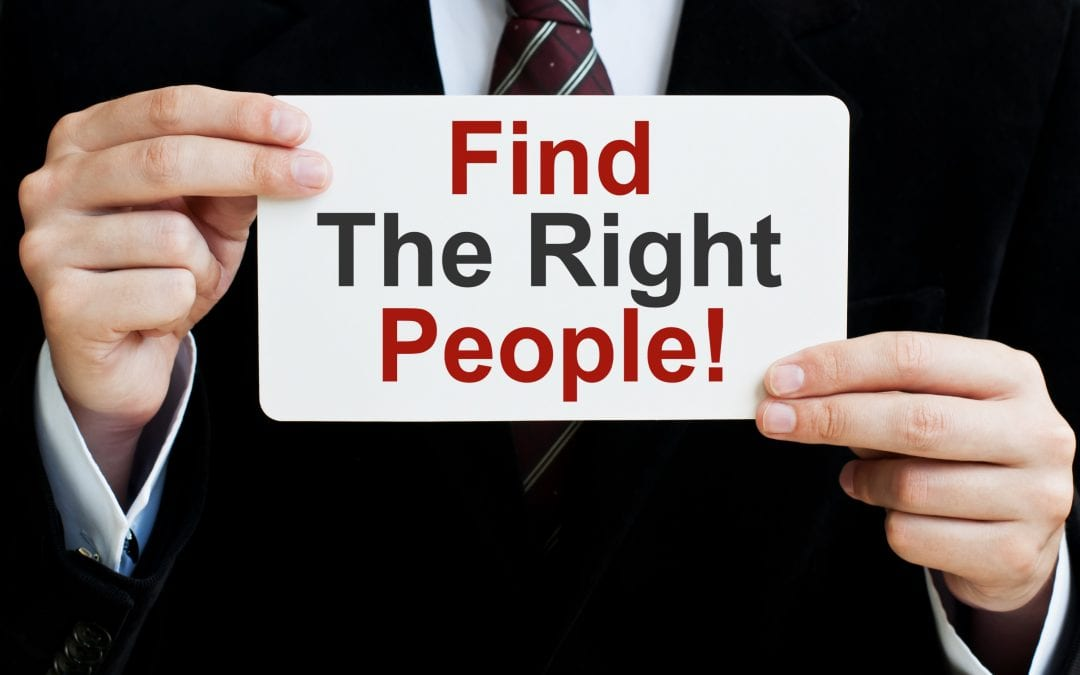 "Business man holding up paper that says ""find the right people"""