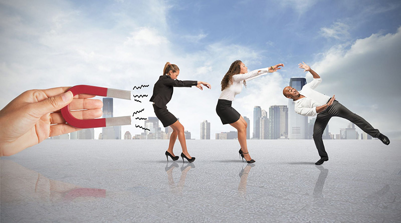 giant hand holding a magnet that is pulling three business people towards it with a big city skyline in the background