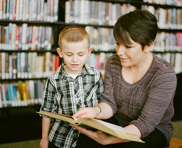 Woman teaching reading to a little boy student and pointing to page.