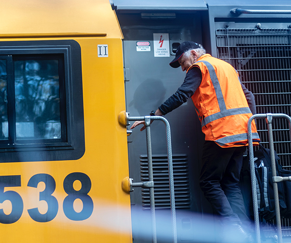 Transportation worker standing on the outside of a train