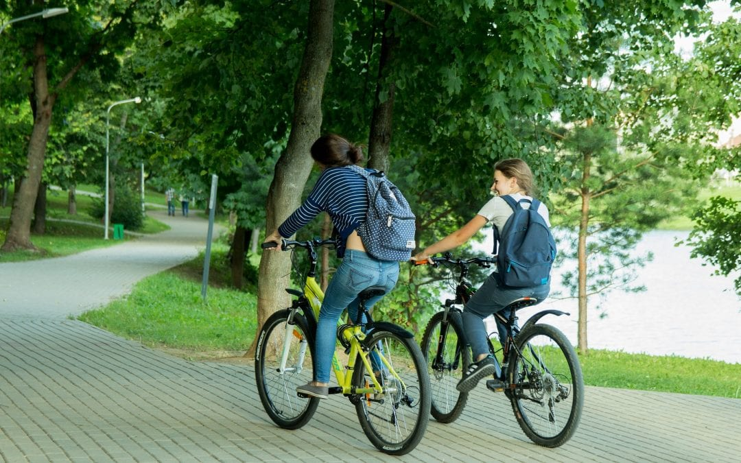Two people biking together along river path